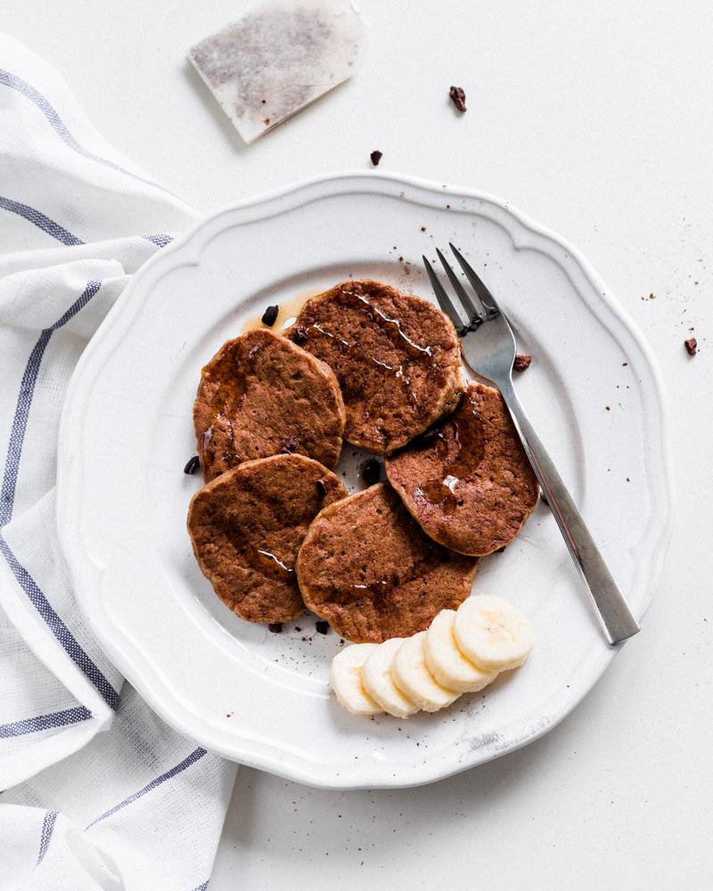 Fünf Pancakes auf einem Teller mit einer Gabel und ein paar Bananenscheiben auf der Seite