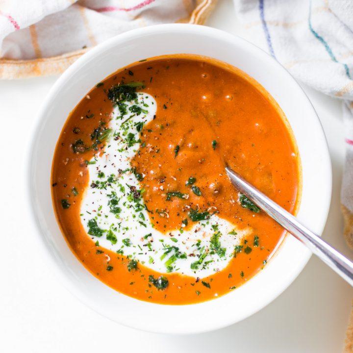 tomaten linsen suppe in schüssel mit kokosmilch und einem löffel