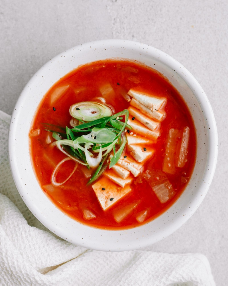 eine weiße schüssel mit veganer kimchisuppe, tofu und frühlingszwiebel